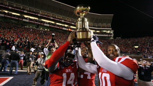Ole Miss' Serderius Bryant (14), Ole Miss' Keith Lewis (24) and Ole Miss' C.J. Johnson (10) raise the Egg Bowl trophy. Mississippi State played Ole Miss in a college football game on Saturday, Nov. 29, 2014 at Vaught-Hemingway  Stadium in Oxford, Miss. (Photo by Keith Warren)