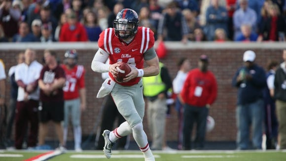 Ole Miss' Bo Wallace (14) rolls out to pass. Mississippi State played Ole Miss in a college football game on Saturday, Nov. 29, 2014 at Vaught-Hemingway  Stadium in Oxford, Miss. (Photo by Keith Warren)