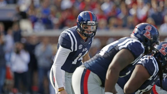 Ole Miss quarterback Bo Wallace talks to his offensive linemen earlier this season.