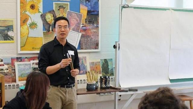 Mr. Hu instructing the class about traditional Chinese brushes to be used for Calligraphy