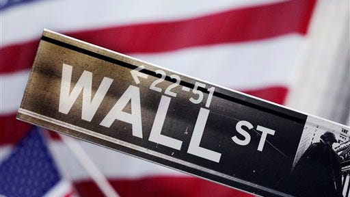 FILE - This Aug. 9, 2011, file photo, shows a Wall Street street sign near the New York Stock Exchange, in New York. A strong jobs report pushed up the stock market higher Thursday, July 3, 2014, with the Dow Jones industrial average crossing 17,000 for the first time. The Department of Labor said employers added 288,000 workers in June, and the unemployment rate fell to 6.1 percent.