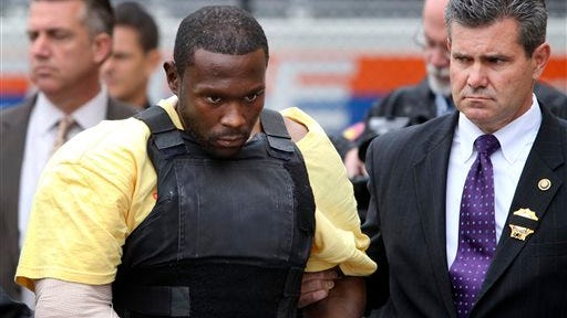 In this Oct. 25, 2012, file photo, Darrell Fuller is escorted out of a police station in Mineola, N.Y. Fuller, who was convicted in July 2014 of killing a police officer during a traffic stop and then a motorist while he was fleeing was sentenced Friday to life in prison.