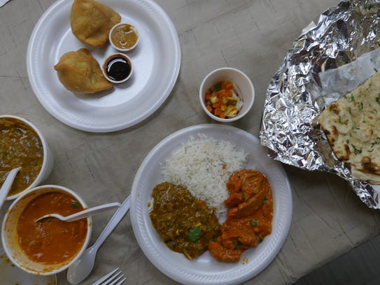 A spread of samosas, garlic naan, sag paneer and butter