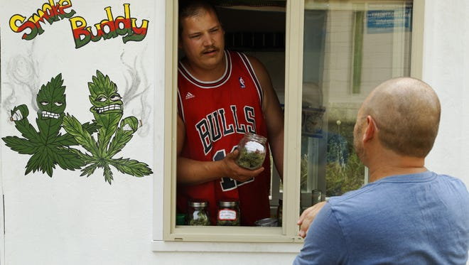 In this Saturday, Aug. 22, 2015 photo, Matt Stein talks with Larry, who declined to give a surname, in the Smoke Buddy mobile medical marijuana cart, parked in the St Johns neighborhood of Portland, Ore.