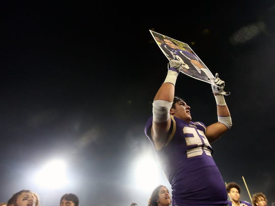 North Kitsap's Dax Solis holds a picture of former teammate Hunter Schaap, who died in February, following Friday's state tournament win over W.F. West.
