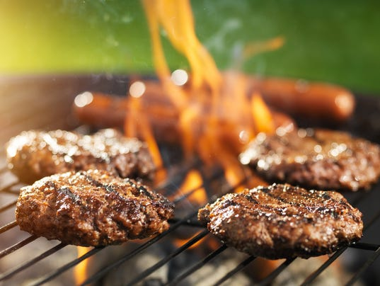 hamburgers and hotdogs cooking on flaming grill