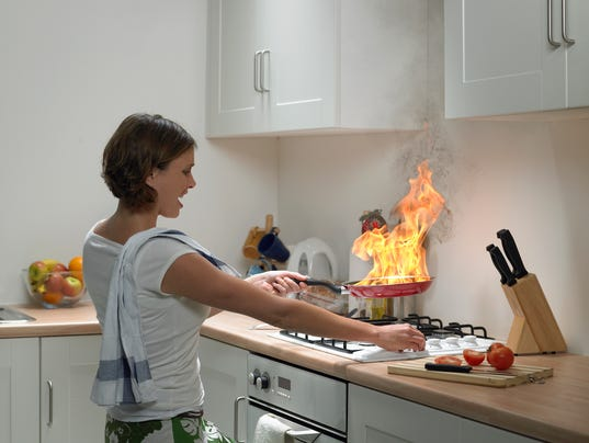 Woman with anguished expression holding burning frying pan in domestic kitchen