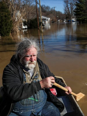 Rick Skees paddles through the floodwaters in Utica Monday morning. Skees' home has about two feet of water so he's been sleeping in his truck with his two dogs. 'This river has more good days than bad days. This is just one of the bad days,' Skees said. He's been using a boat to check on his home and to cook some food on a camp stove for himself and his dogs.