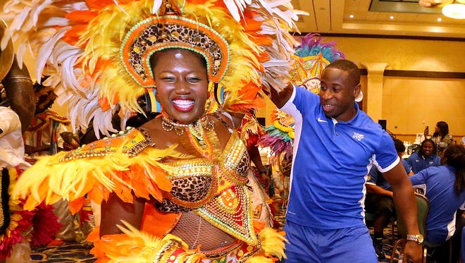 MTSU football player Cavellis Luckett dances with a Junkanoo dancer during a welcome reception at the Atlantis Paradise Island resort on Sunday in the Bahamas.