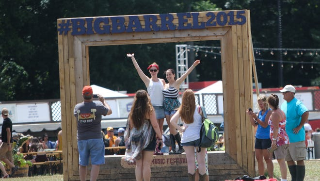 Fans take photos at a Big Barrel sign on the final day of the Big Barrel Country Music Festival last year.