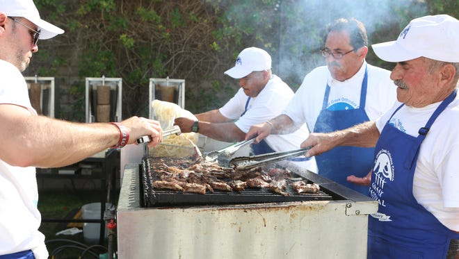 Adam Burns, left, and his grandfather Frank Fakinos, left, grill lamb during the 20th Annual Greek Festival held at Saint George Greek Orthodox Church in Palm Desert on Saturday, February 27, 2016.