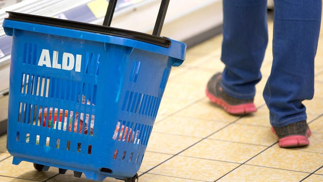 A customer uses a blue plastic shopping basket, branded with the Aldi name, as they shop inside an Aldi supermarket store in London in June. In the United States, Aldi is mounting a challenge to retail giant Wal-Mart.