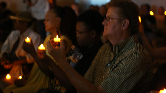 Community members of Desert Hot Springs hold candles in silence during a peace vigil held inside the Henry Lozano Community Center on Thursday, June 16, 2016.