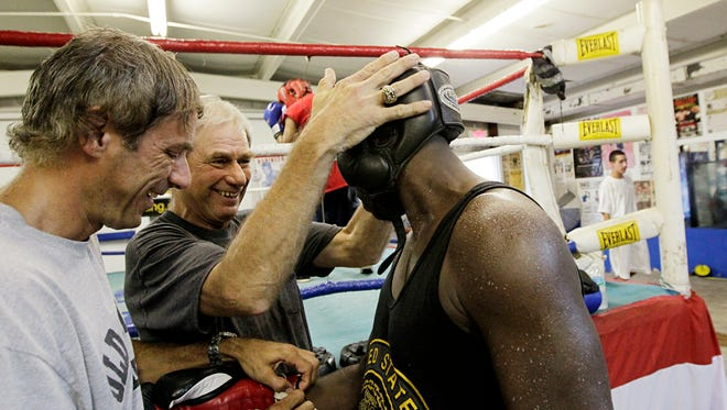 Steve Canton, center, Barr's manager and trainer for the past 16 years, and his brother, Chris Canton, left, who assists at the gym, secures Barr's head gear before a sparring session on Tuesday, Aug. 17, 2010.