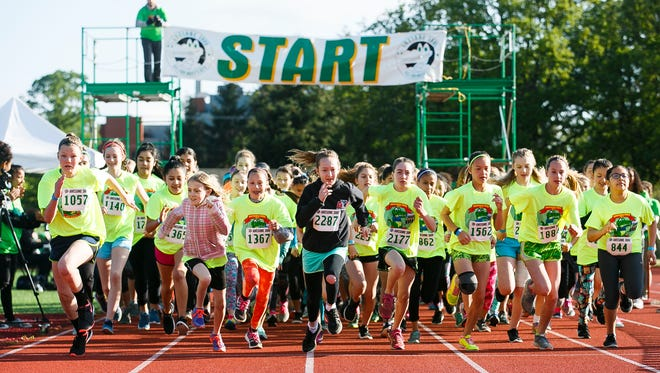 Middle school and high school girls take off at the 35th annual Awesome 3000 on Saturday, May 6, 2017, at McCulloch Stadium in Salem, Ore.