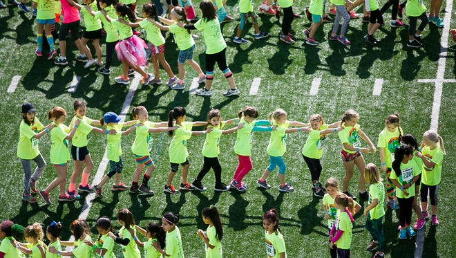 Second graders form a long conga line in their corral as they wait for the start of their race at the 35th annual Awesome 3000 on Saturday, May 6, 2017, at McCulloch Stadium in Salem, Ore.
