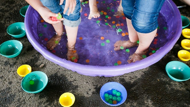 Myers Elementary students try to grasp floating balls with their feet at Field Day on Friday, June 16, 2017, in Salem.
