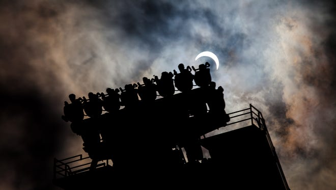 Riders on Cedar Point's Valravn roller coaster hang over the edge and prepare to take a 214-foot dive straight down to Earth while the sun disappears behind them during the 2017 solar eclipse.
