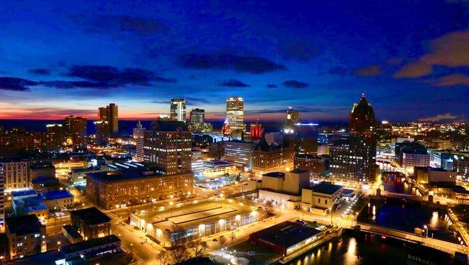 The sun rises behind the Milwaukee skyline.
