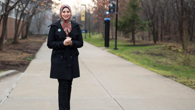 Suehaila Amen, coordinator of International Admissions and Recruitment at the University of Michigan-Dearborn, is seen on campus, Thursday, Dec. 10,in Dearborn, Mich. Amid the high level of harassment, threats and vandalism directed at American Muslims and at mosques, Muslim women are intensely debating the duty and risks related to wearing their head-coverings as usual.