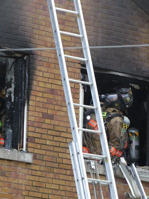 Firefighters work to extinguish a house fire on Shirley Place in West Price Hill Monday. No one was injured.