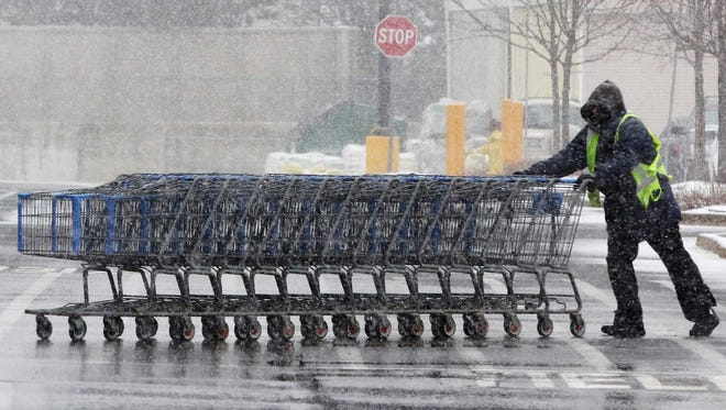 Jerry Helinski pushes shopping carts in the snow at Walmart in Lake Zurich, Ill., as a winter storm impacted the suburbs of Chicago on Tuesday, March 1, 2016.