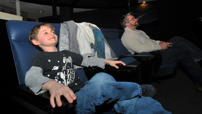 Ren Gunning, 8, of Wausau, pushes his seat back to get comfortable for the Season of Light show at Wausau West High School planetarium.
