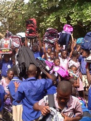 Children in Ghana show off the book bags and other educational materials they received from the Charles Kyeremeh Jr. Foundation, an organization created by Bertha and Charles Kyeremeh Sr. started after their 20-year-old son was killed in a motorcycle crash five years ago.