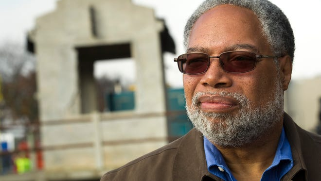 """Lonnie Bunch, founding director of The National Museum of African American History and Culture, stands in front of the guard tower from Louisiana State Penitentiary, also known as """"Angola"""" and """"The Farm"""" before it was lowered into the museum's construction site in Washington, Sunday, Nov. 17, 2013. The tower, part of the museum's inaugural exhibition on segregation, is too large to install after the building is complete. Instead, it will be installed during construction and the museum will be completed around it."""