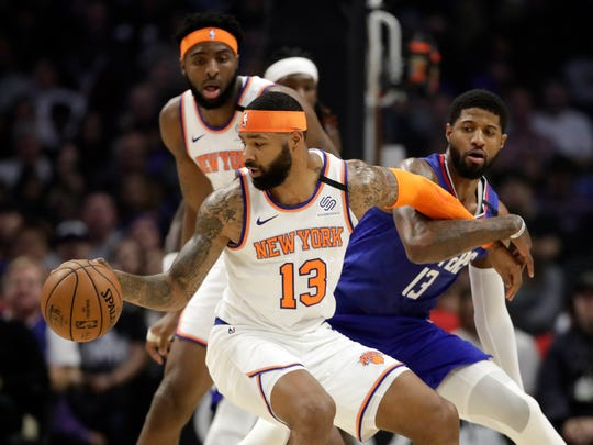 New York Knicks' Marcus Morris Sr., front left, is defended by Los Angeles Clippers' Paul George, right, during the first half of an NBA basketball game Sunday, Jan. 5, 2020, in Los Angeles. (AP Photo/Marcio Jose Sanchez)