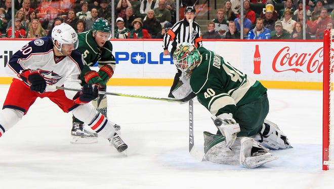 Columbus Blue Jackets left wing Brandon Saad (20) shoots on Minnesota Wild goalie Devan Dubnyk (40) as Wild's Christian Folin defends during the second period of an NHL hockey game Saturday, Dec. 31, 2016, in St. Paul, Minn. (AP Photo/Andy Clayton-King)