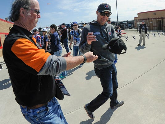 Pole winner Kevin Harvick, right, gives attention to a fan as he leaves a drivers meeting before a NASCAR Monster Cup series auto race at Atlanta Motor Speedway in Hampton, Ga., Sunday, March 5, 2017. (AP Photo/John Amis)