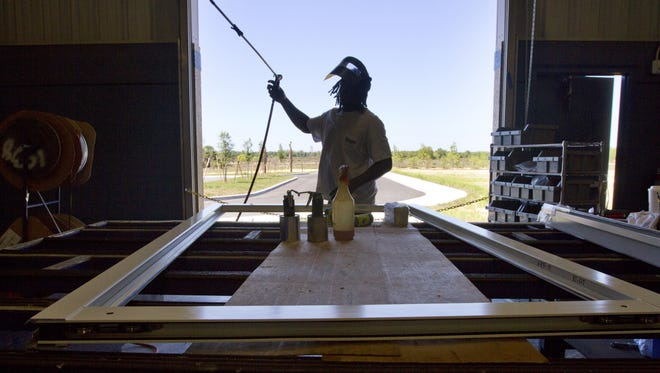 Timothy Simpson of Fort Myers assembles a metal sliding door frame while working at Eastern Architectural Systems, a division of Eastern Metal Supply, in Fort Myers.
