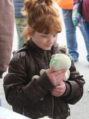 A little girl holds a stuffed toy she won at a special