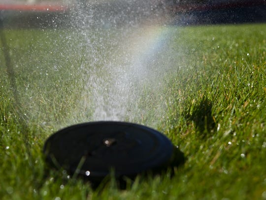 A rainbow shines through the water in a sprinkler.