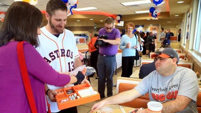 Houston Astros infielder Tyler White delivers a meal to Sherri Seals (left) and Trey Seals during the Houston Astros Caravan on Thursday, Jan. 19, 2017, at Whataburger in Corpus Christi.