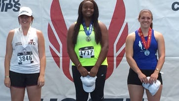 Amity's Lindsay McShane (right) stands on the medal stand after placing second in the hammer throw Monday.