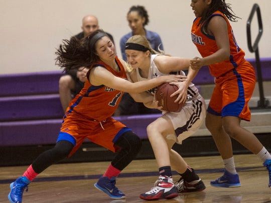 Cape Coral's Meka Sillevis tries to strip the ball from Cypress Lake's Emily Slone in the 5A-3 girls basketball regional semifinal at Cypress Lake High School on Tuesday, February 10, 2015.