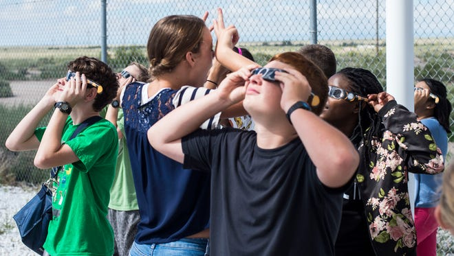 Visiting students from a local middle school view the sun via special solar-filtered glasses during the eclipse at the solar observatory at Holloman Air Force Base, N.M., Aug. 21, 2017. This eclipse, last viewed from American soil Feb. 26, 1979, was visible to citizens across the continental United States, traversed Holloman AFB, appeared as a partial solar eclipse at 10:23 a.m. MST that lasted a total of 2 hours and 53 minutes.