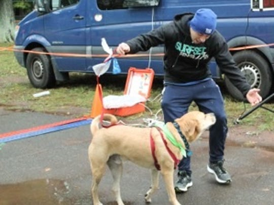 A runner in the annual Good Dog Rescue's Annual 5K and Doggy Dash Doggy Dash celebrates with his companion as they cross the finish line in Nomahegan Park last year.