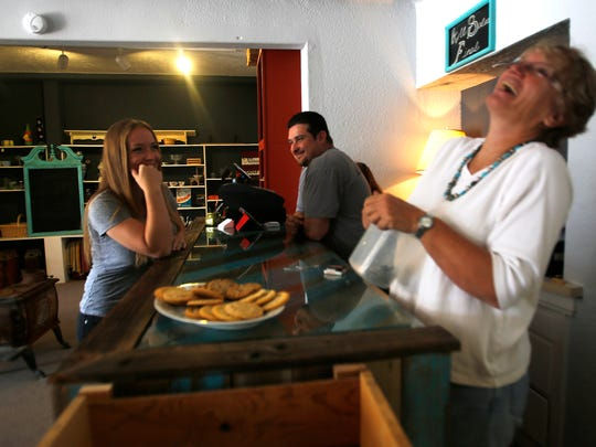 Sarah Herrera, left, Max Herrera and Rebecca Smith talk Wednesday at their store, Downtown Junkers in Farmington.