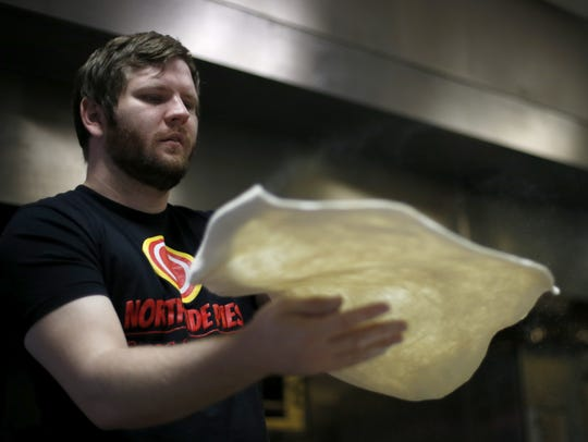 Jeremy Matlow, co-owner of Northside Pies, is shown preparing dough for a pizza at his restaurant in June 2017.