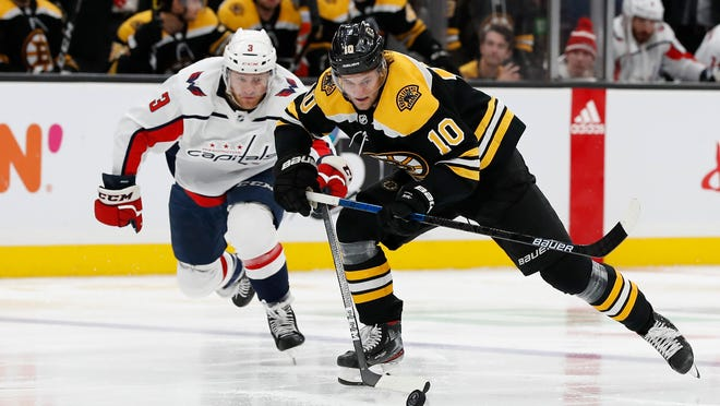 Boston Bruins' Anders Bjork beats Washington Capitals' Nick Jensen to the puck during the second period of an NHL hockey game Monday, Dec. 23, 2019, in Boston.
