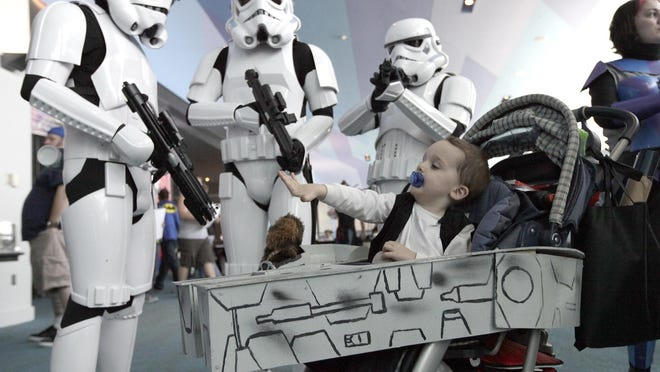 SATURDAY SEPTEMBER 17, 2011 COMICS LOCALThomas Wells, 2, from Hamilton, OH, as Han Solo aboard The Millennium Falcon, actually his stroller, seems unaware of the presence of Storm Troopers from the same Star Was adventure. Costumes were on display at the CIncinnati Comic Expo at Duke Energy Center downtown. The Enquirer/Michael E. Keating
