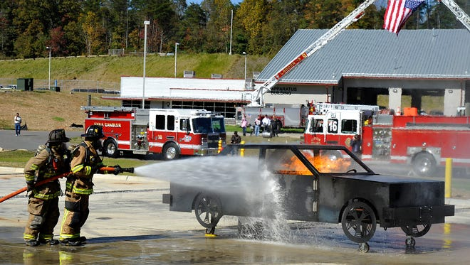 In this 2012 photo, Skyland firefighters Kevin Bartlett and Brandon Munsey work to extinguish a practice fire at the Buncombe County Public Safety Training Facility during opening ceremonies in Woodfin.