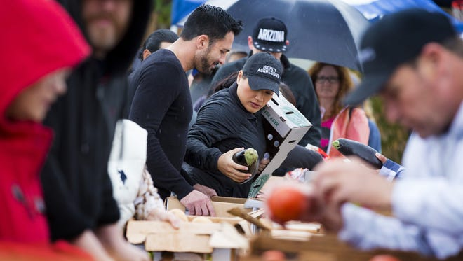 Victor Fraire, 38, left, and Terri Slezak, 32, of Peoria, shop early Saturday morning in the rain at Produce on Wheels-With Out Waste at Faith Bible Church in Glendale. Produce on Wheels-With Out Waste sells 60 pounds of fresh rescued produce for $10.