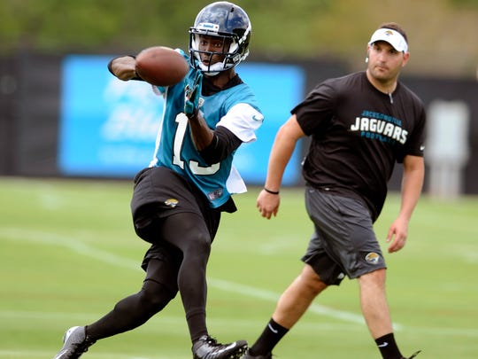 Jacksonville Jaguars wide receiver Mohamed Massaquoi (13) catches a pass under the watchful eye of Jaguars offensive quality control coach Tony Sorrentino during a voluntary veteran NFL football mini-camp,  Tuesday, April 16, 2013, in Jacksonville, Fla. (AP Photo/Stephen Morton)