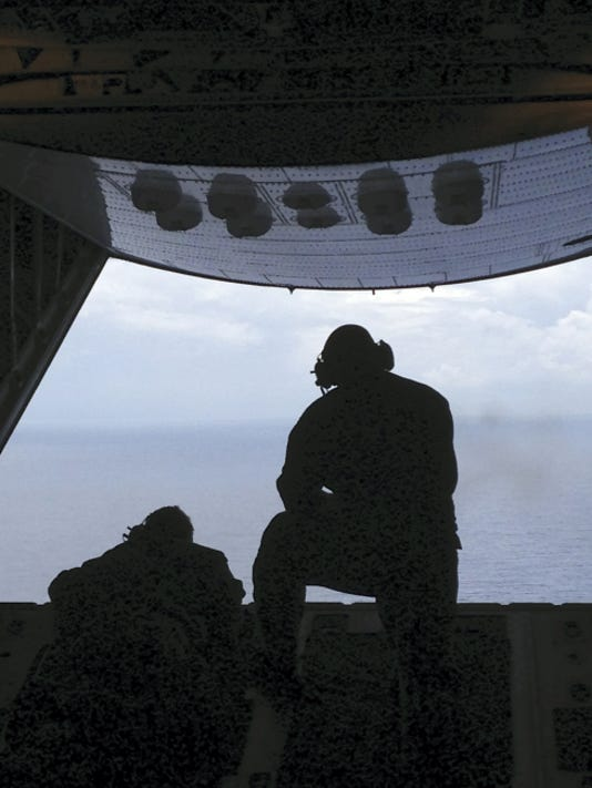 Petty Officer 3rd Class Charles Camarda, left, and Petty Officer 3rd Class Nate Matthews scour the Atlantic Ocean off the coast of Savannah, Ga., Tuesday, July 28, 2015, looking for two missing teenage boaters. Camarda and Matthews are crew members from Air Station Clearwater, Florida. (AP Photo/Tamara Lush)