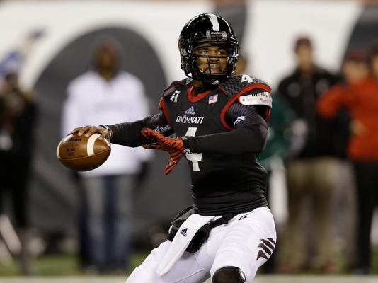 FILE - In thisOoct. 4, 2014, file photo, Cincinnati quarterback Munchie Legaux (4) passes against Memphis in the second half of an NCAA college football game in Cincinnati. Legaux, who overcame a horrific leg injury at the University of Cincinnati, is one of 25 players invited by the Bengals to a predraft tryout at Paul Brown Stadium. (AP Photo/Al Behrman, File)