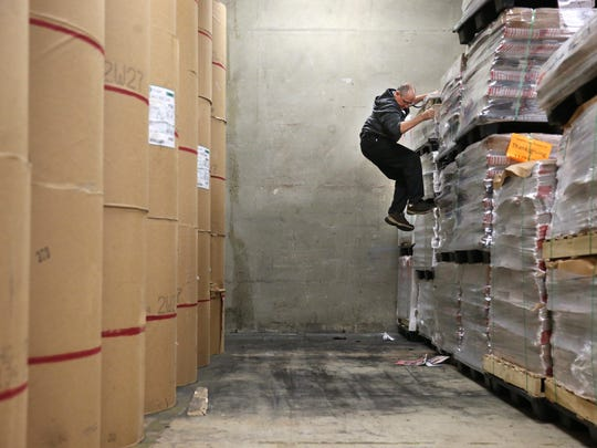 Packaging Manager Ken Rice scales a wall of inserts for Thursday's paper in the Tallahassee Democrat warehouse Tuesday.